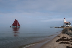 "A traditional Dutch sailing boat approaches the ""Horse of Marken"" lighthouse, Isle of Marken, The Netherlands"